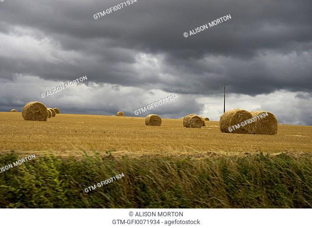 Hay bales and dark skies