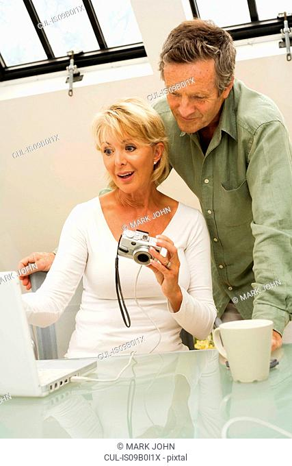 Couple uploading from digital camera to computer on home desk