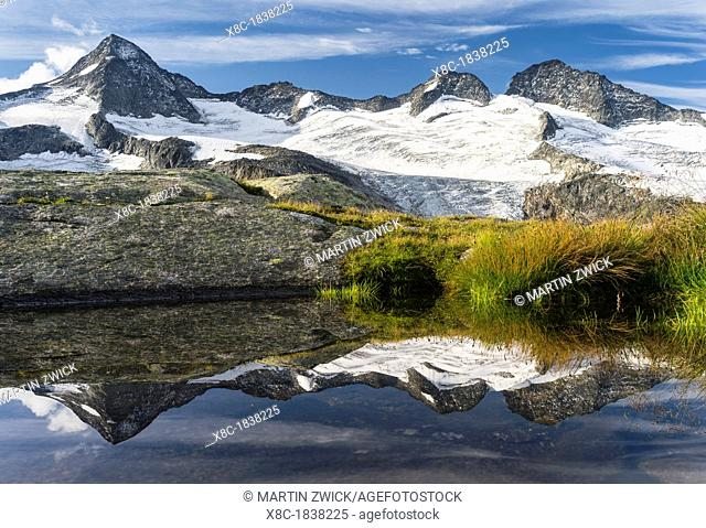 Valley head of valley Obersulzbachtal in the NP Hohe Tauern  The Peaks of Mt  Grosser Geiger and Mt  Maurerkeeskopf with a perfect reflection in a glacial pond...