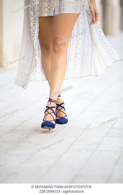 Close up of woman's feet wearing blue stiletto walking on the pavement