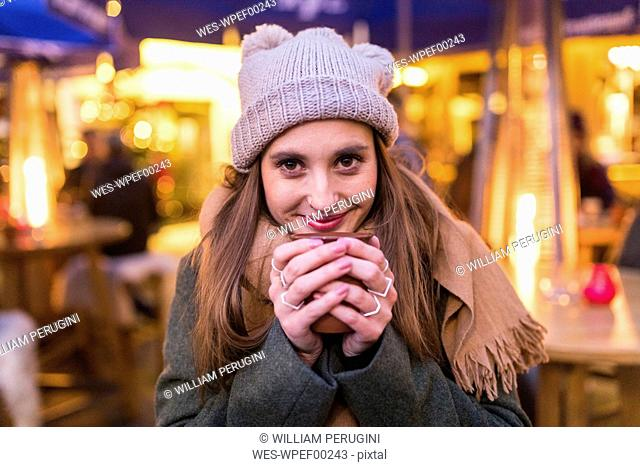 Portrait of content young woman drinking mulled wine at Christmas market