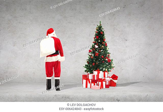 ptesents, holidays and people concept - man in costume of santa claus with bag over concrete wall and christmas tree background