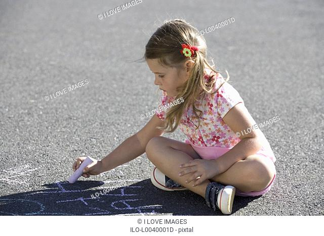 Young girl writing in chalk on the playground
