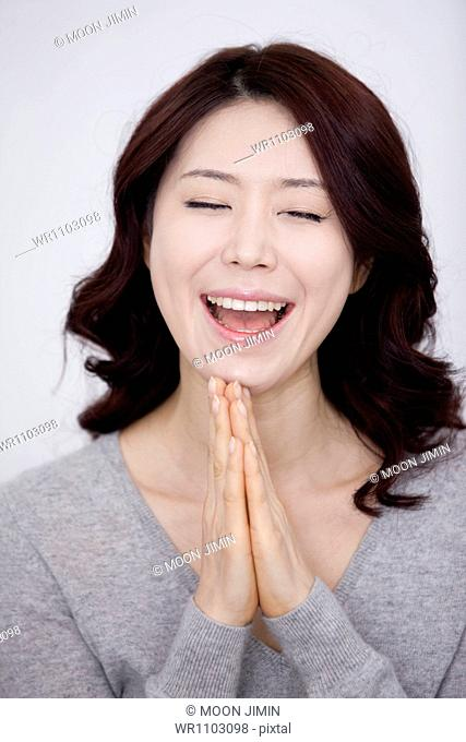 a woman in grey plain shirt smiling