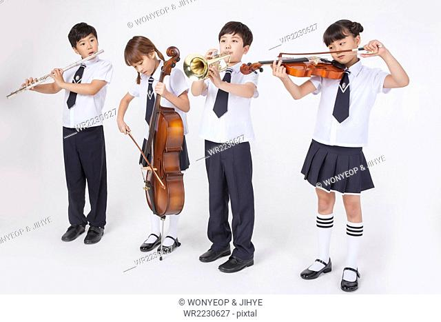 Four elementary school students in school uniforms standing next to each other and playing a classical musical instrument each