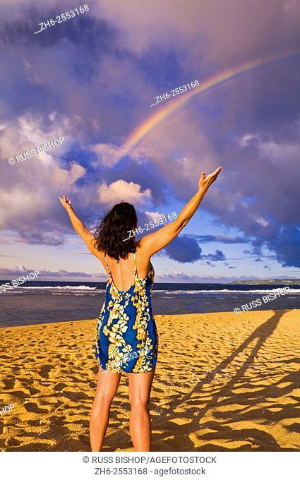Rainbow over woman raising arms on Tunnels Beach at sunset, Island of Kauai, Hawaii