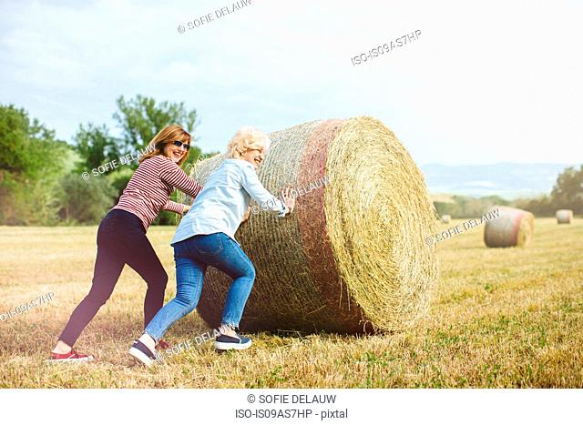 Two mature female friends pretending to push straw bale, Tuscany, Italy