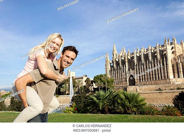 Spain, Mallorca, Palma, Couple smiling with St Maria Cathedral in background, portrait