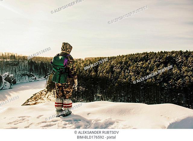 Caucasian hiker standing on snowy hilltop