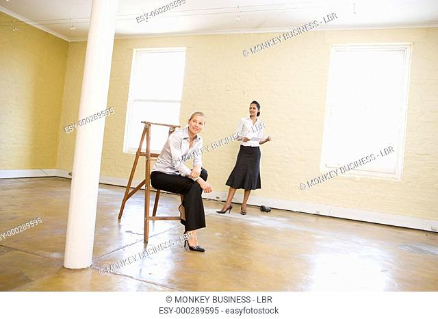 Two women with ladder in empty space holding paper smiling