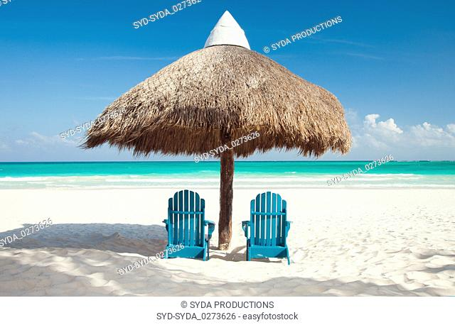 two sun chairs under palapa on tropical beach