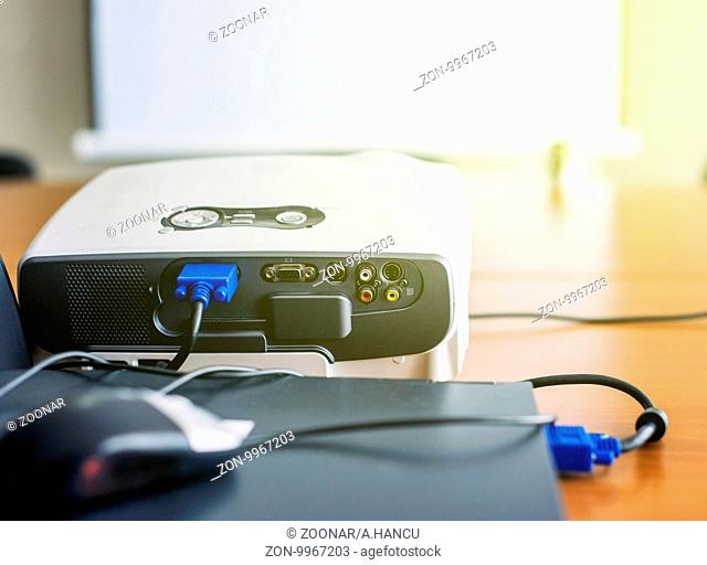 Closeup of projector for presentation connected to laptop with blank screen in front in sunny conference room