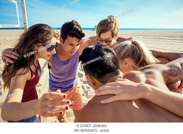 Group of friends in huddle on beach