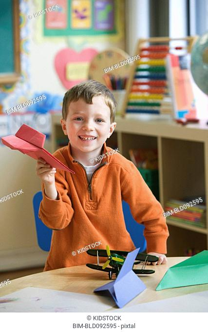 Caucasian boy making paper airplane in classroom