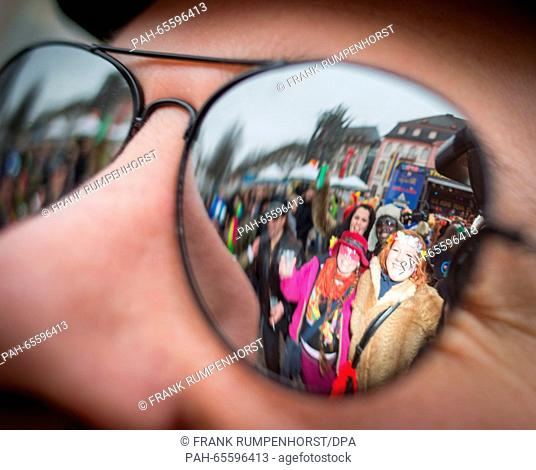 A Carnival enthusiasts mirror in the sunglasses of a Carnival visitor during the street Carnival festivities in Mainz, Germany, 4 February 2016