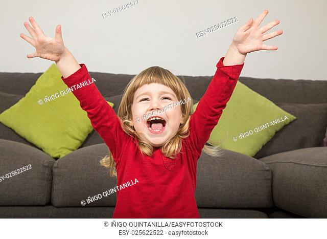 funny portrait of three years old child, with red and green clothes, hands up, laughing and shouting happy indoor home