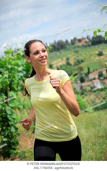 Young woman jogging in a vineyard