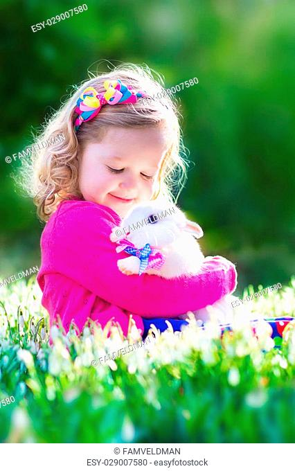 Adorable little girl, cute curly toddler in a colorful summer dress, playing with a real rabbit, having fun with her pet bunny in a beautiful garden with first...