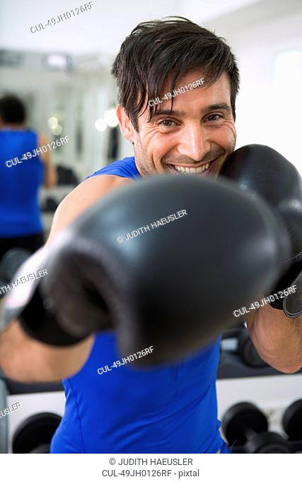 Boxer wearing boxing gloves in gym
