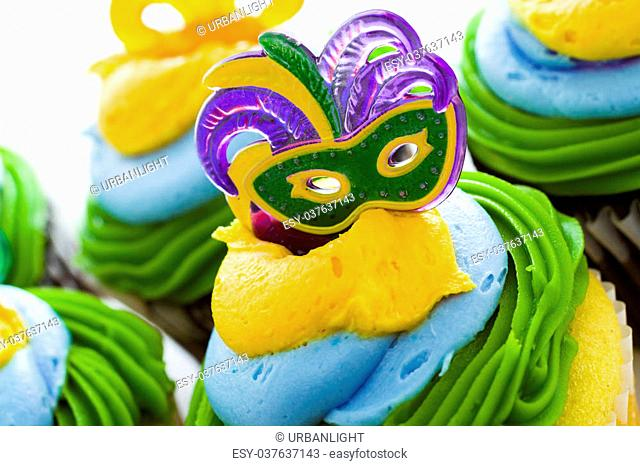 Fancy cupcakes decorated with leaf and mask for Mardi Gras party