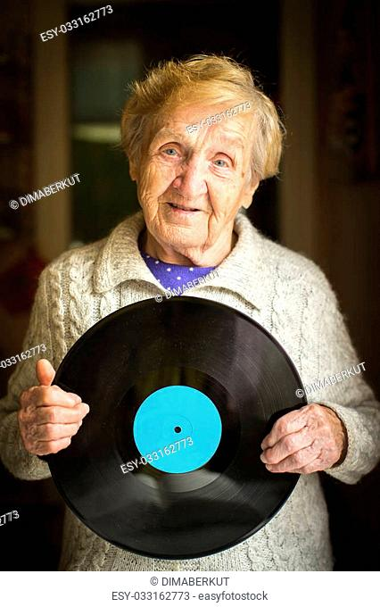 Elderly woman with the vinyl lp record in his hands. Place on vinyl for your text