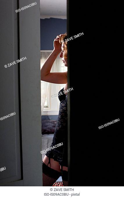 Woman in bedroom seen through open door