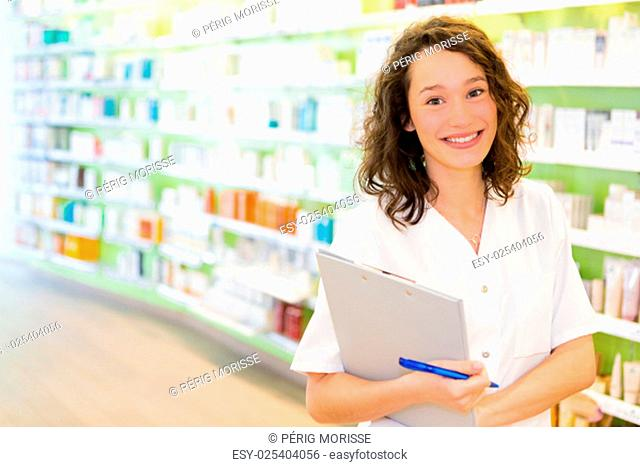 View of an Attractive pharmacist taking notes at work
