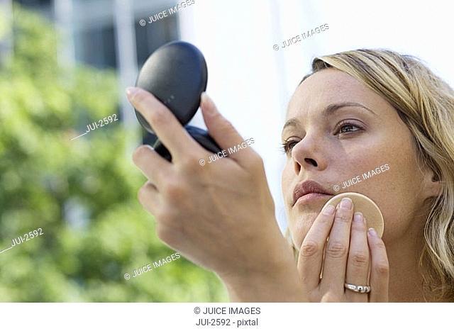 Young blonde woman applying make-up using powder compact, close-up