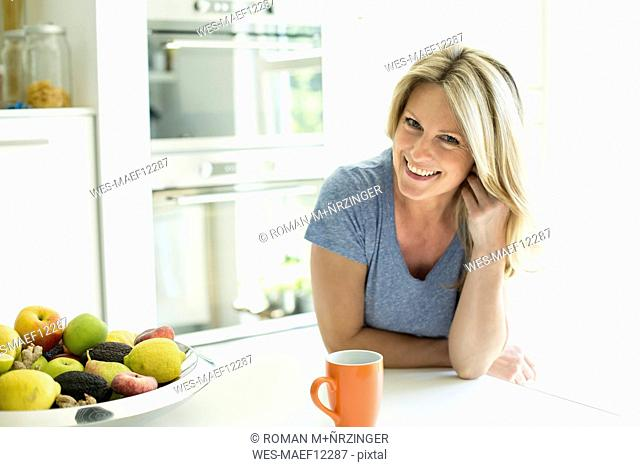Portrait of smiling woman at home with cup of coffee and fruit bowl