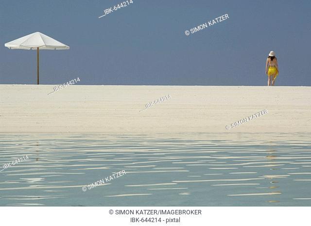 Woman and parasol on the beach, Diffushi Island, Holiday Island, Southern Ari Atoll, Maldives, Indian Ocean