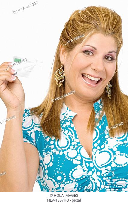 Portrait of a mature woman showing a credit card and smiling