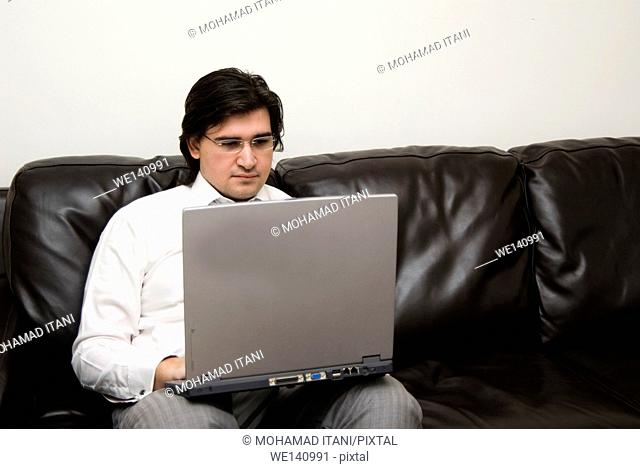 Man on leather sofa working on laptop computer