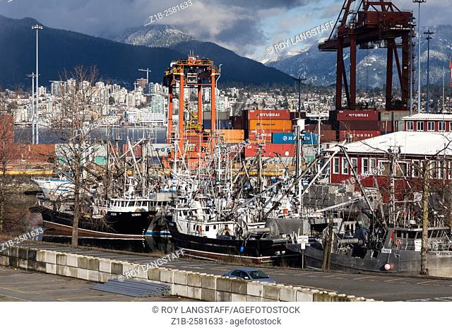 Fishing vessels and container cranes in the dock area of Vancouver, Canada