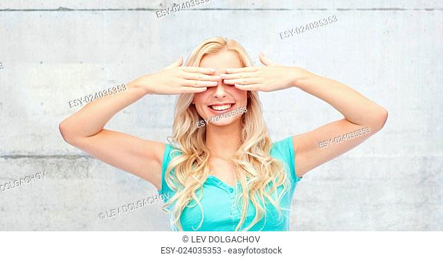 emotions, expressions and people concept - smiling young woman or teenage girl covering her eyes with palms over gray concrete wall background