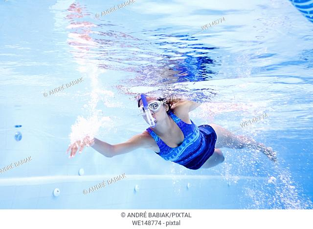 Young woman practicing swimming in lap pool with swimmer snorkel and googles