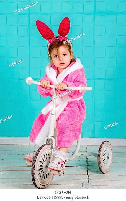 Little cute girl in pink rabbit costume sits on an old tricycle