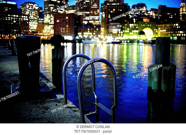 Metal ladder along commercial pier with Boston Waterfront in background