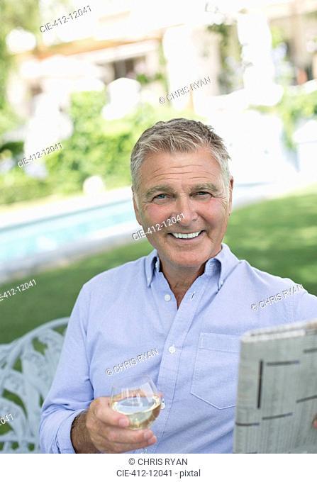 Senior man reading newspaper and drinking wine in backyard