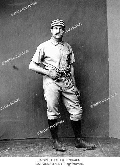 A photographic portrait of Sid Farrar in a Philadelphia Quakers uniform, in the photograph he is posing casually in a studio with one hand on his belt