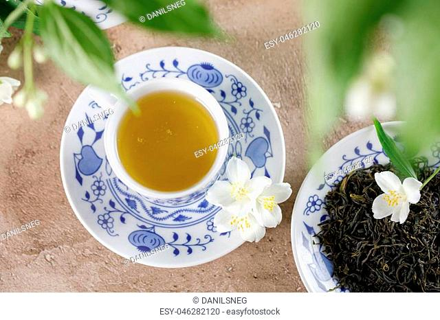 A cup of green tea with a taste of jasmine. Still life with fresh flowers. View from above