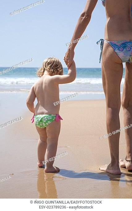summer back family of two years old blonde baby with pink and green swimsuit holding hand with brunette woman mother in bikini standing at sea shore beach sand...