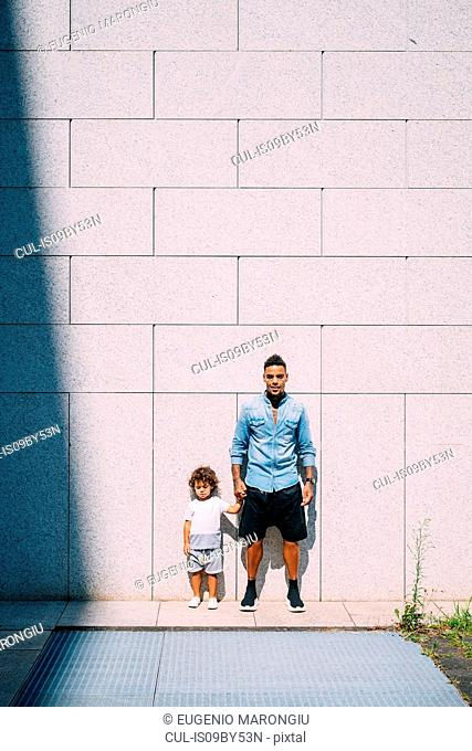 Father and son standing against concrete wall