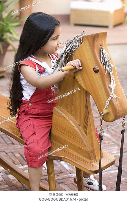 Young girl playing on wooden rocking horse