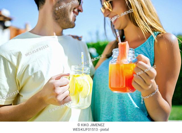 Couple holding refreshing drinks outdoors
