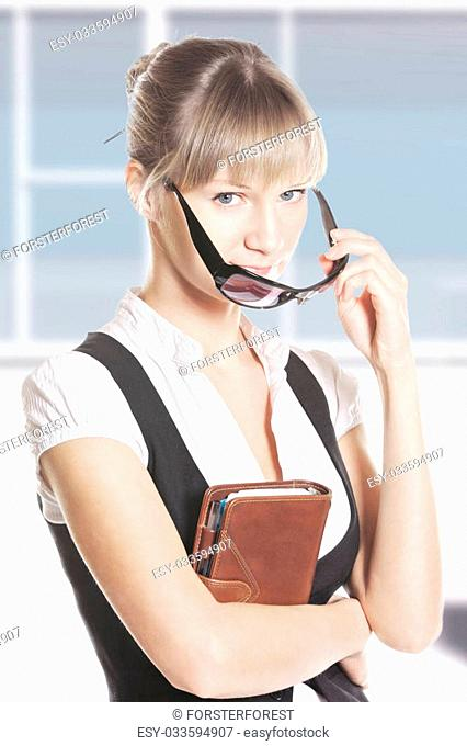 Caucasian woman with leather notebook looking over sunglasses at office