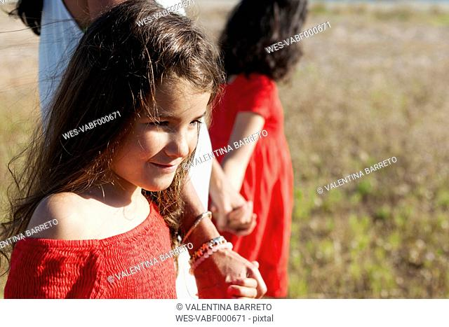 Portrait of smiling little girl walking hand in hand with her mother and sister