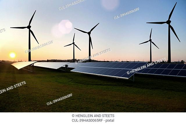 Wind turbines and solar panels in field