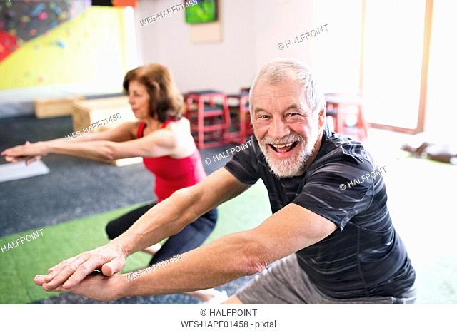 Senior man and woman exercising in gym