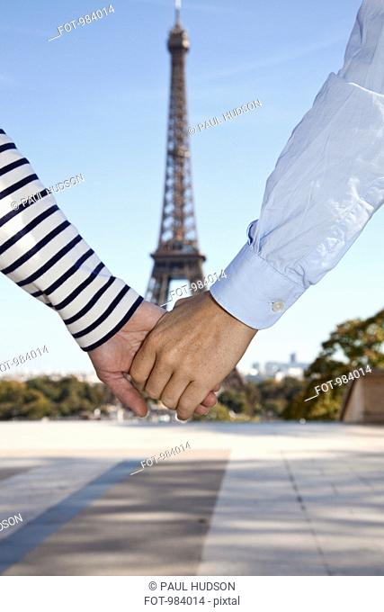 A man and woman holding hands in front of the Eiffel Tower, focus on hands