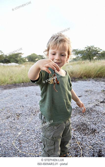 Portrait of young boy holding scorpion, Otavi, Etosha, Namibia